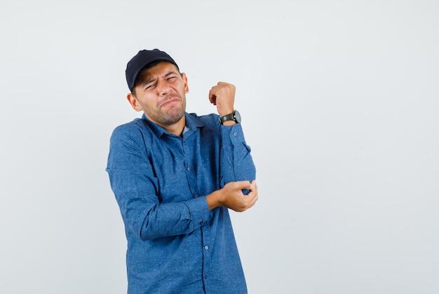 Jonge man die lijdt aan pijnlijke elleboog in blauw shirt, pet, vooraanzicht.