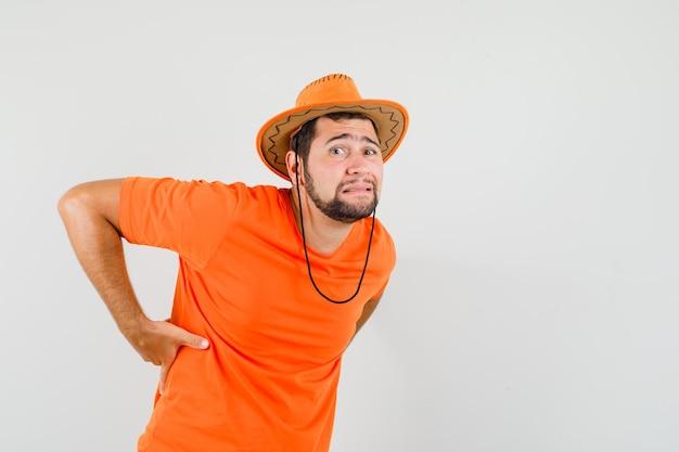 Jonge man die lijdt aan rugpijn in oranje t-shirt, hoed en er vermoeid uitziet. vooraanzicht.