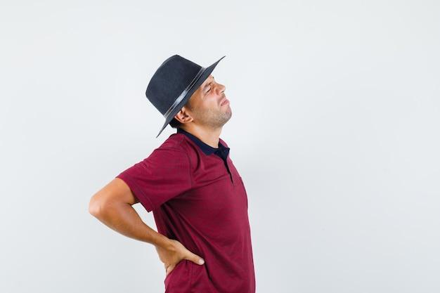 Jonge man die lijdt aan rugpijn in t-shirt, hoed en er moe uitziet.
