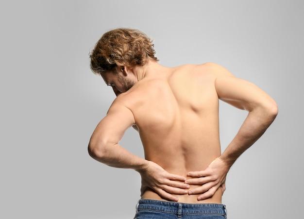 Jonge man die lijdt aan rugpijn op lichte ondergrond