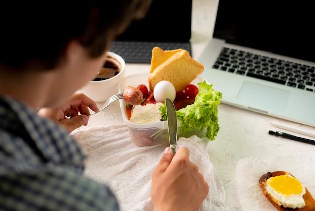 Jonge man die maaltijd voor de laptop neemt tijdens het werken, concepten voor slechte gewoontes en obesitas