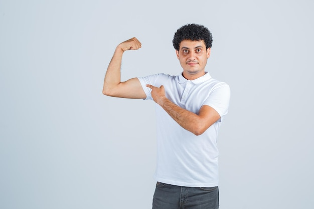 Jonge man die machtsgebaar toont in wit t-shirt en spijkerbroek en er krachtig uitziet, vooraanzicht.