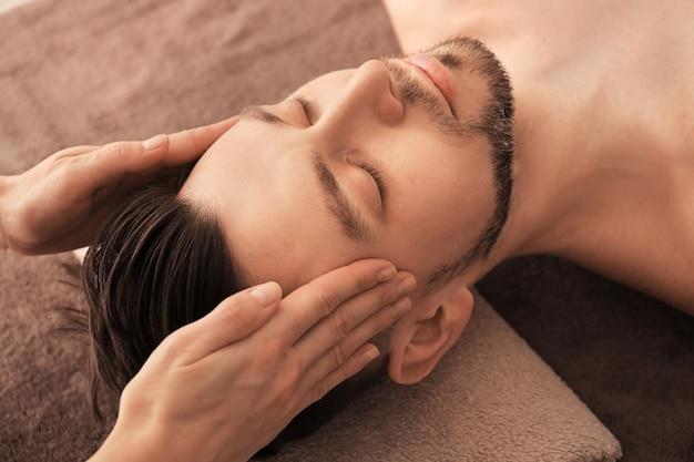 Jonge man die massage ontvangt bij kuuroordsalon