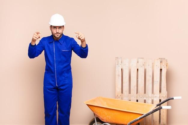 Jonge man die met beide vingers en een boze uitdrukking naar de camera wijst, zegt dat je je plicht bouwconcept moet doen