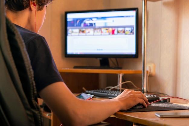 Jonge man die met de computer werkt en thuis op een toetsenbord typt, freelancer-concepten