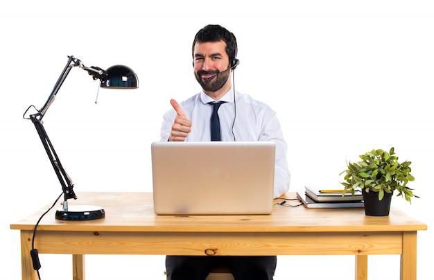 Jonge man die met een hoofdtelefoon met duim omhoog werkt