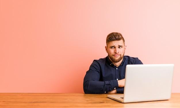Jonge man die met zijn laptop in de war werkt, voelt zich twijfelachtig en onzeker