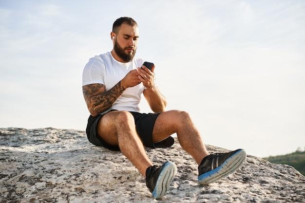 Jonge man die mobiele telefoon gebruikt tijdens een wandeling op het platteland