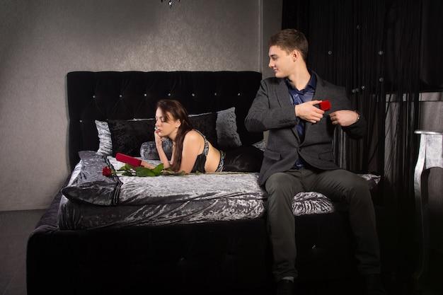 Jonge man die moed verzamelt om voor te stellen zittend op het einde van het bed in zijn pak te kijken naar zijn vriendin die naar haar valentijnscadeau kijkt terwijl hij de rode ringdoos uit zijn zak haalt