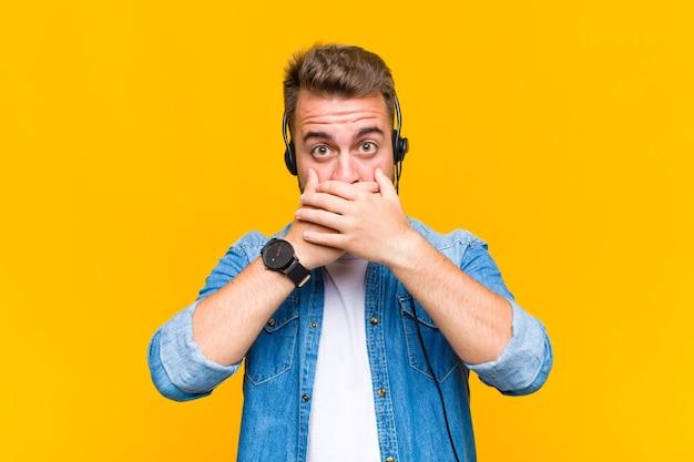 Jonge man die mond bedekt met handen met een geschokte, verbaasde uitdrukking, een geheim bewaren of oeps zeggen