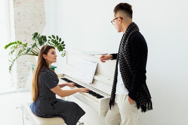 Jonge man die mooie vrouw het spelen piano bekijkt