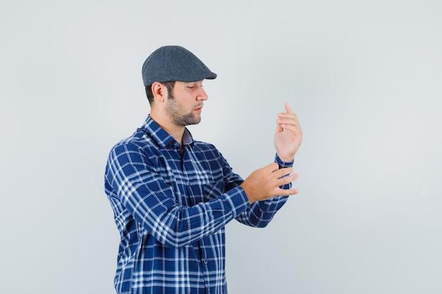 Jonge man die mouw van zijn overhemd in overhemd, pet dichtknoopt en er knap uitziet, vooraanzicht. Gratis Foto