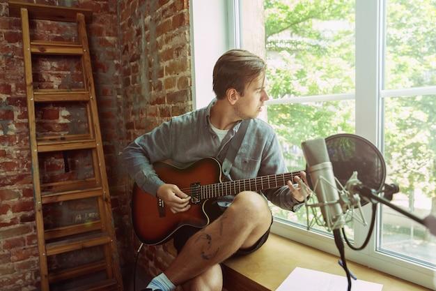 Jonge man die muziekvideoblog, huisles of zang opneemt, gitaar speelt of uitzending van internetlessen maakt terwijl hij op de zolderwerkplek of thuis zit