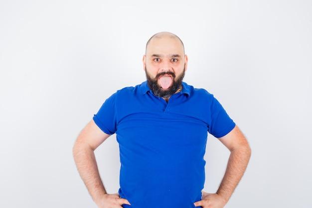 Jonge man die naar de camera kijkt met de hand op de taille, tong uitsteekt in het vooraanzicht van het blauwe shirt.