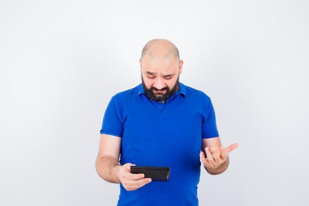 Jonge man die naar de rekenmachine kijkt terwijl hij de hand met open palm in een blauw shirt houdt en er verward uitziet. vooraanzicht.