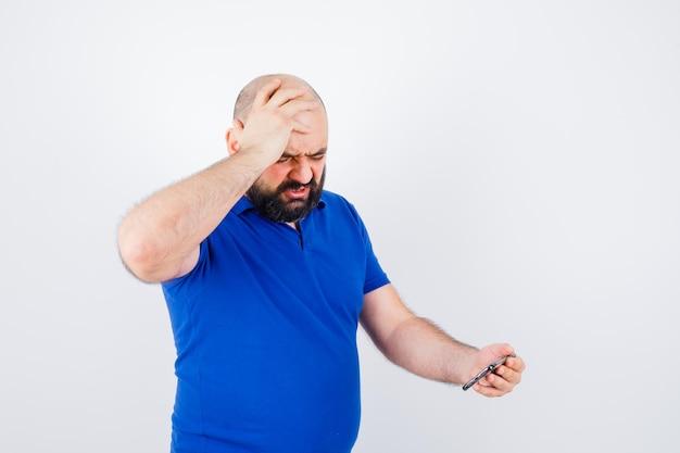 Jonge man die naar de telefoon kijkt terwijl hij de hand op het hoofd houdt in een blauw shirt en er agressief uitziet, vooraanzicht.