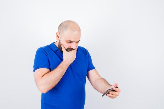 Jonge man die naar de telefoon kijkt terwijl hij in een blauw shirt denkt en peinzend kijkt. vooraanzicht.