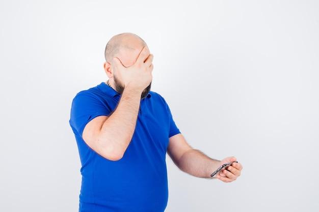 Jonge man die naar de telefoon kijkt terwijl hij zijn gezicht bedekt met de hand in een blauw shirt en er stressvol uitziet. vooraanzicht.