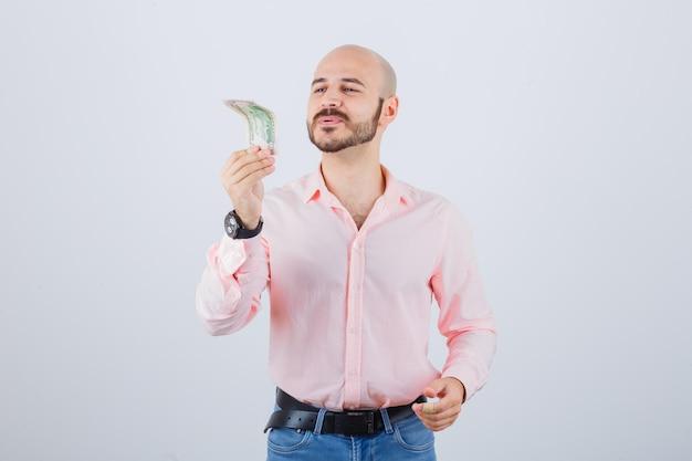 Jonge man die naar geld kijkt terwijl hij in een roze shirt blaast, jeans vooraanzicht.