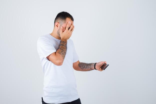 Jonge man die naar iets op de telefoon kijkt en zijn gezicht bedekt met de hand in een wit t-shirt en een zwarte broek en er geïrriteerd uitziet