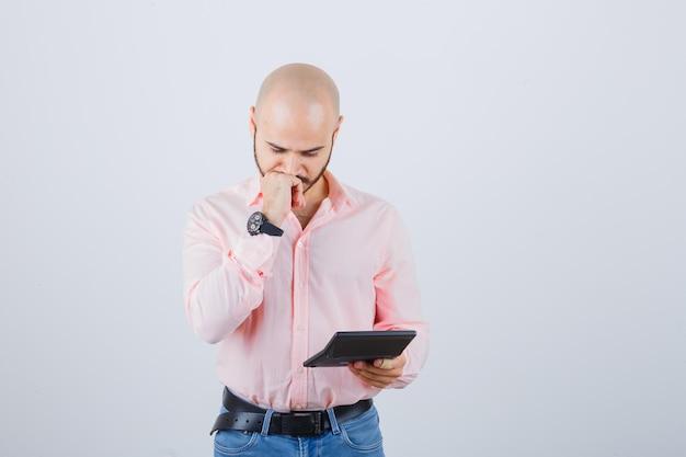 Jonge man die naar rekenmachine kijkt terwijl hij in roze shirt, spijkerbroek, vooraanzicht denkt.