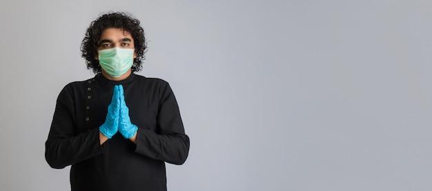 Jonge man die namaste doet vanwege het uitbreken van covid-19. nieuwe begroeting om de verspreiding van coronavirus te voorkomen in plaats van te begroeten met een knuffel of handdruk. yogapraktijk voor mentaal evenwicht.