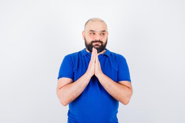 Jonge man die namaste-gebaar in blauw shirt toont en dankbaar kijkt, vooraanzicht.