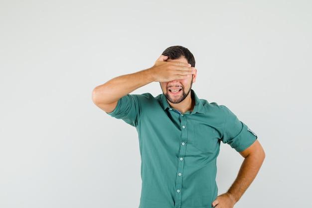 Jonge man die ogen bedekt met zijn hand in groen shirt en verlegen kijkt. vooraanzicht.