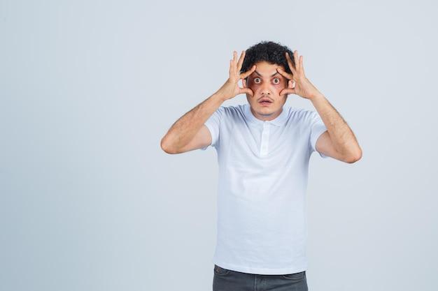 Jonge man die ogen opent met handen in wit t-shirt, broek en gefocust, vooraanzicht.