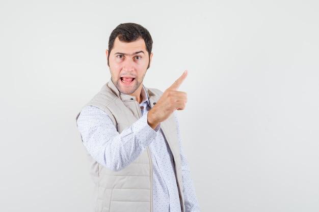 Jonge man die omhoog wijst en tong uitsteekt in beige jas en op zoek optimistisch. vooraanzicht.