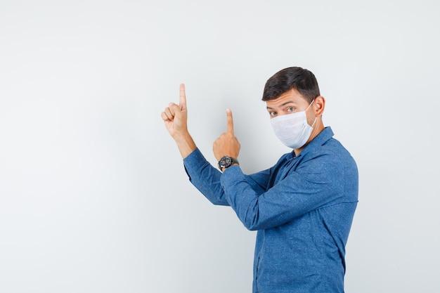Jonge man die omhoog wijst in een blauw shirt, masker en er serieus uitziet. .