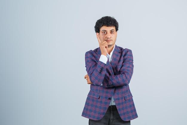 Jonge man die omhoog wijst in shirt, jas, broek en er intelligent uitziet. vooraanzicht.