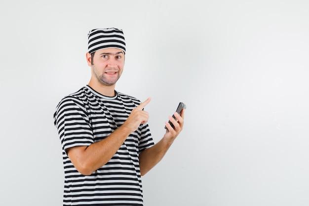 Jonge man die omhoog wijst, rekenmachine in t-shirt, hoed houdt en er verstandig uitziet. vooraanzicht.
