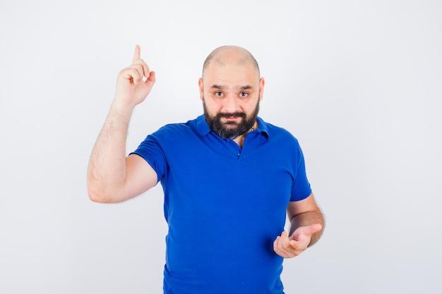 Jonge man die omhoog wijst terwijl hij naar de camera in een blauw shirt kijkt en er gefocust uitziet. vooraanzicht.