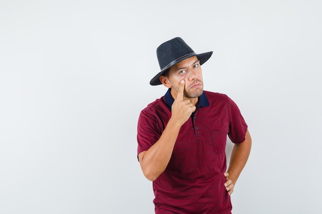 Jonge man die onderste ooglid naar beneden trekt met vinger in t-shirt, hoed en sarcastisch kijkt, vooraanzicht.