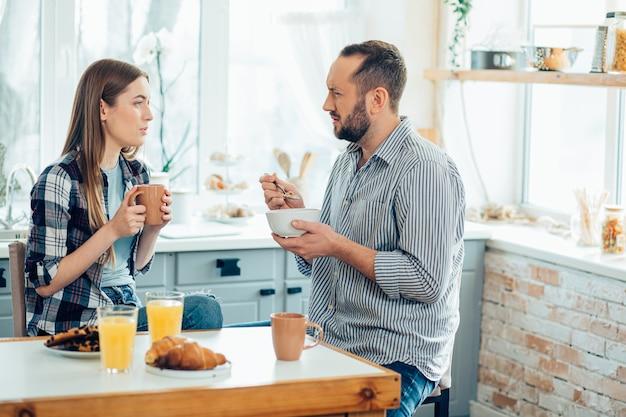 Jonge man die ontbijtgranen eet en fronst terwijl hij naar de jonge dame kijkt met thee voor hem