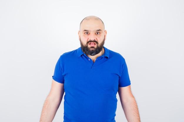 Jonge man die ontevredenheid uitdrukt in blauw shirt en er ontevreden uitziet, vooraanzicht.