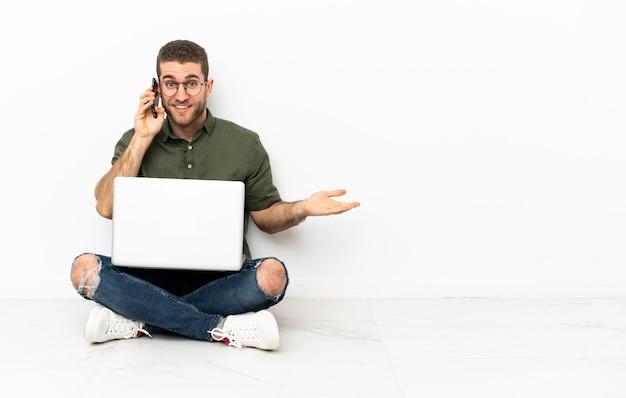 Jonge man die op de grond zit en een gesprek voert met de mobiele telefoon met iemand