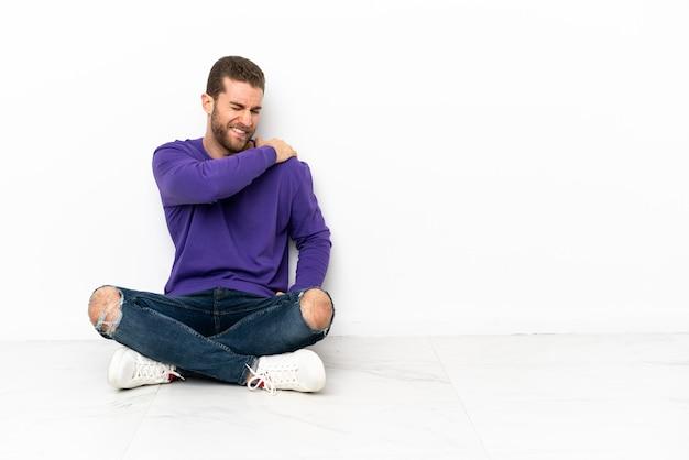 Jonge man die op de grond zit en last heeft van pijn in de schouder omdat hij moeite heeft gedaan