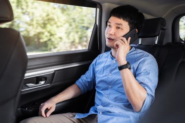 Jonge man die op de mobiele telefoon praat terwijl hij op de achterbank van de auto zit