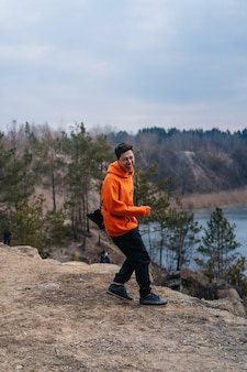 Jonge man die op de rand van een klif