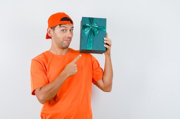 Jonge man die op dit moment doos in oranje t-shirt en pet richt en nieuwsgierig kijkt