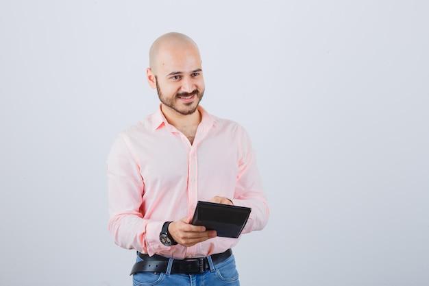 Jonge man die op knoppen van de rekenmachine drukt in een roze shirt, spijkerbroek en er optimistisch uitziet. vooraanzicht.
