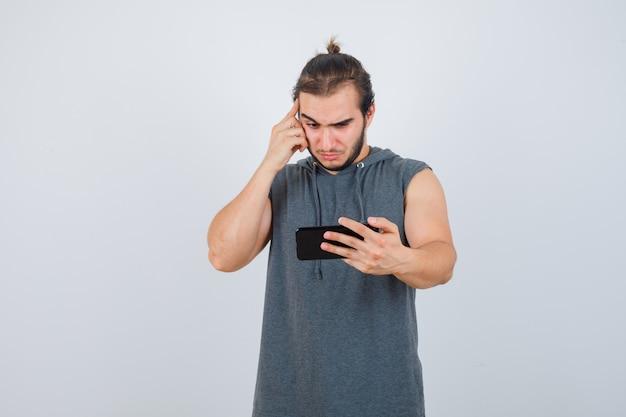 Jonge man die op telefoon in t-shirt met een kap kijkt en nadenkend, vooraanzicht kijkt.