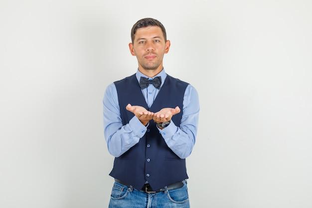 Jonge man die open handpalmen bij elkaar houdt in pak, jeans en er vrolijk uitziet.