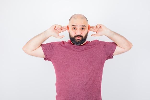 Jonge man die oren aanraakt met vingers in roze t-shirt en er grappig uitziet. vooraanzicht.