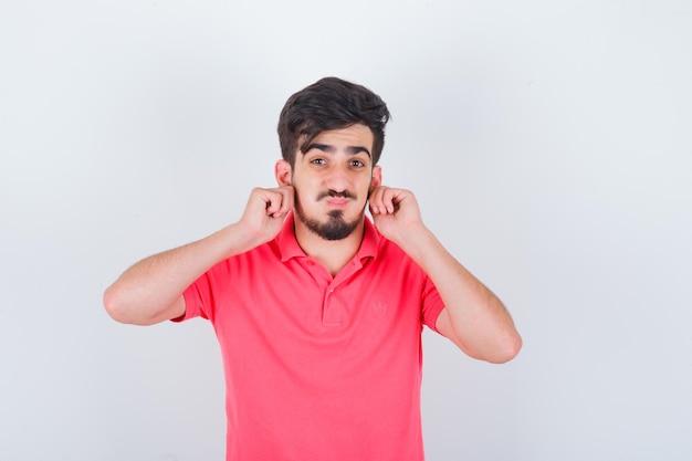 Jonge man die oren naar beneden trekt in een roze t-shirt en er schattig uitziet. vooraanzicht.