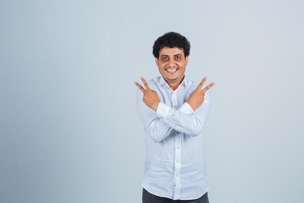 Jonge man die overwinningsgebaar in wit overhemd toont en er vrolijk uitziet. vooraanzicht.