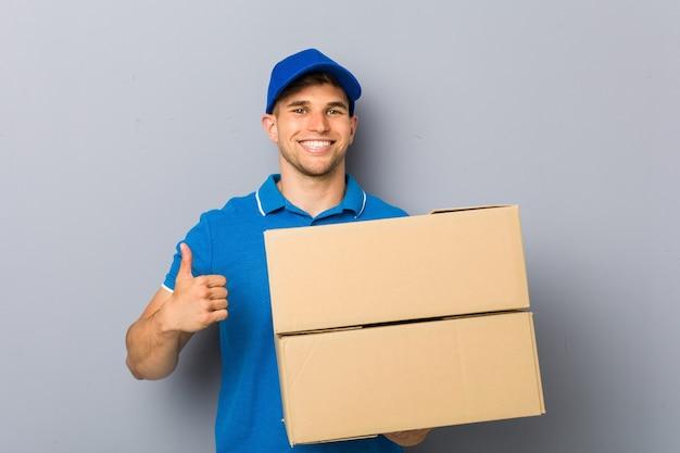 Jonge man die pakketten levert die en duim glimlachen opheft
