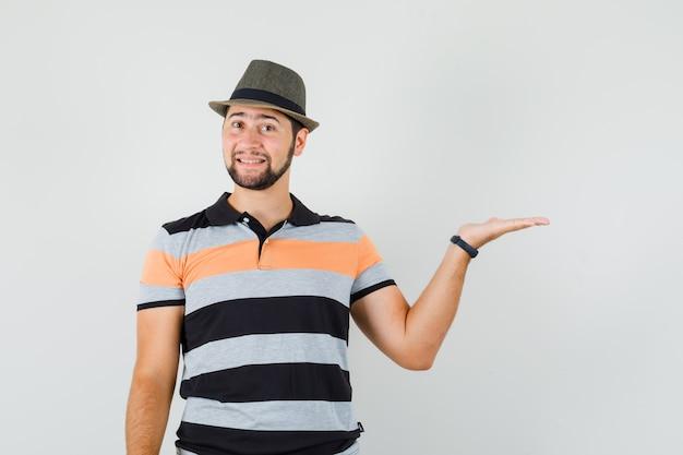 Jonge man die palm opzij in t-shirt, hoed uitspreidt en vrolijk kijkt
